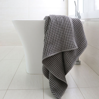 pokoloko-waffle-turkish-towel-dark-grey-drapped-on-end-of-bath-tub-in-bathroom