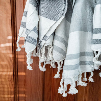 pokoloko-classic-turkish-hand-towel-navy-light-grey-colour-against-door