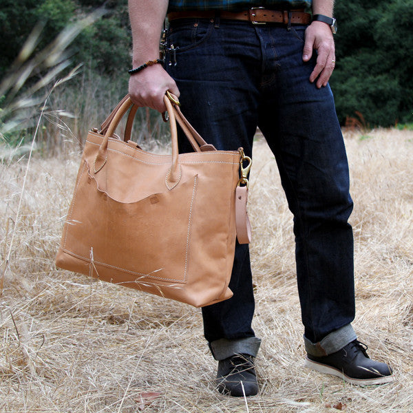 Man carrying large leather veg tan travel bag