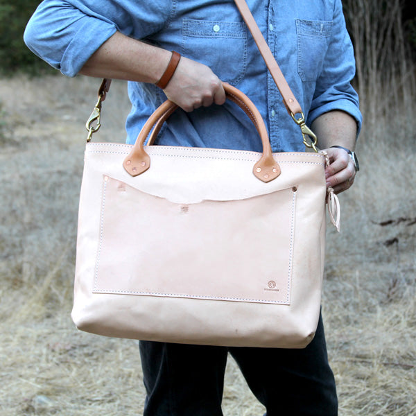 Large veg tan leather bag with shoulder strap with denim outfit