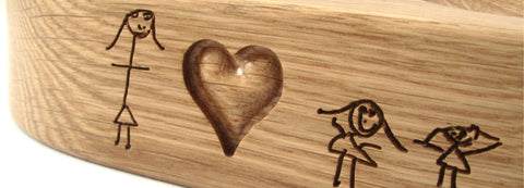 Kids drawing engraved on mobile phone holder in oak