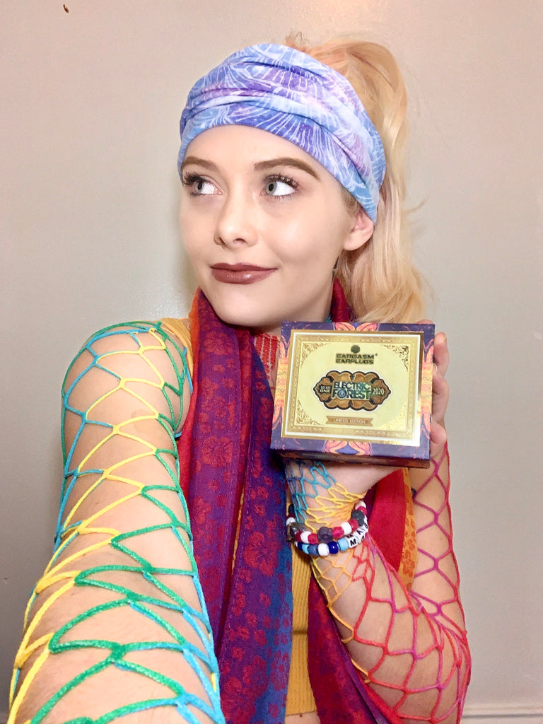 Woman in rainbow outfit holding Limited Edition box of Electric Forest Earplugs.