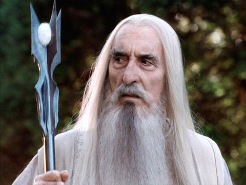 Saruman with a long white beard and his matching white outfit and staff