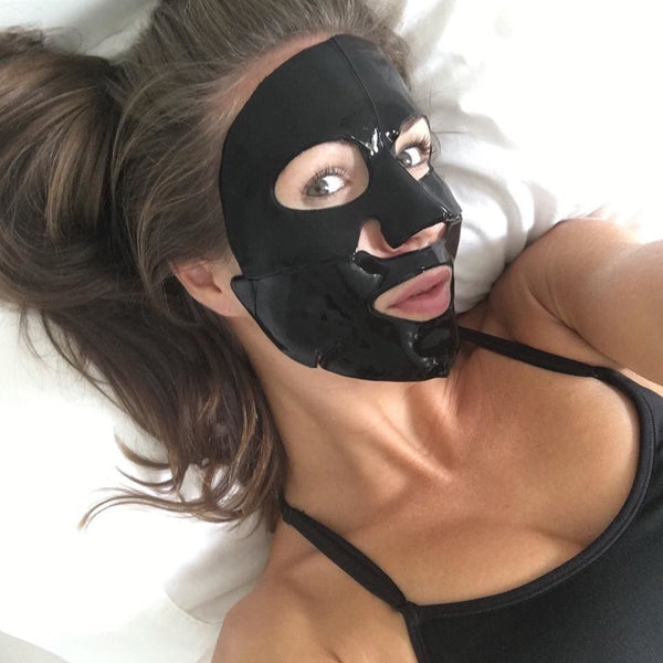 Female using charcoal collegen face mask