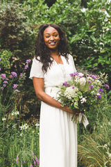Happy girl wearing silk georgette wedding dress with sleeves, standing in a garden, carrying a purple and white bouquet