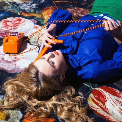 Girl lying on Mooi rug twisting telephone cable