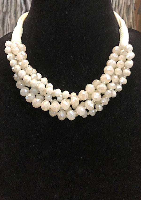 This is a gorgeous statement piece this it's multi strands of lightly twisted, faceted beads.  It's great paired with jeans for a causal look or dress it up for an elegant evening out.    Color - Natural Material - Faceted Beads and Cording Length - 18""