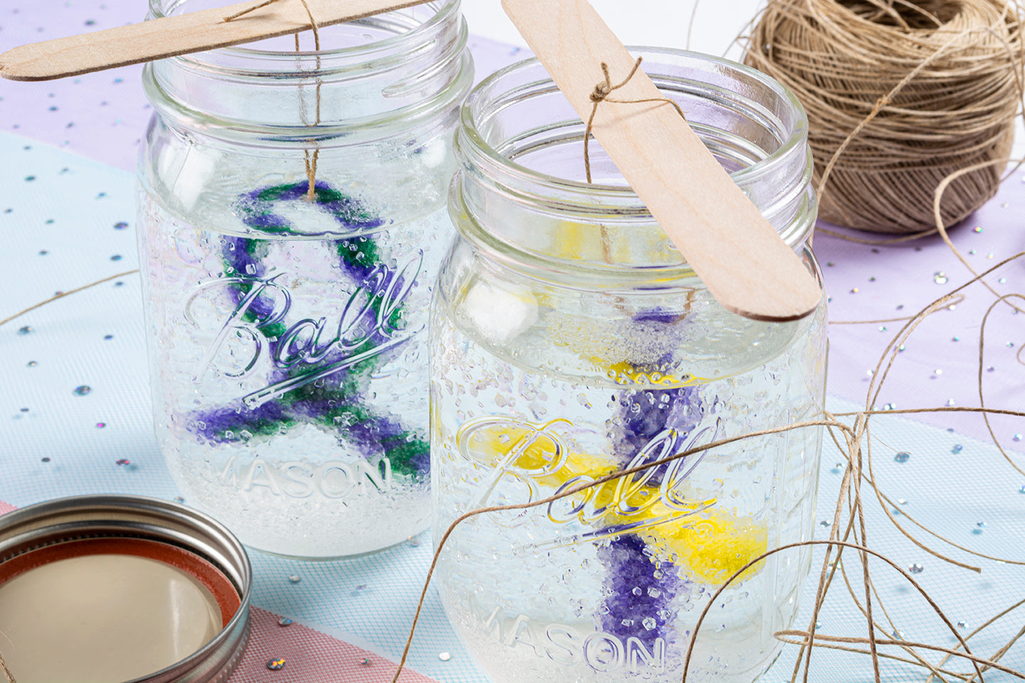 Closeup image of borax pipe cleaner crystals being made in jars with string and sparkles in background