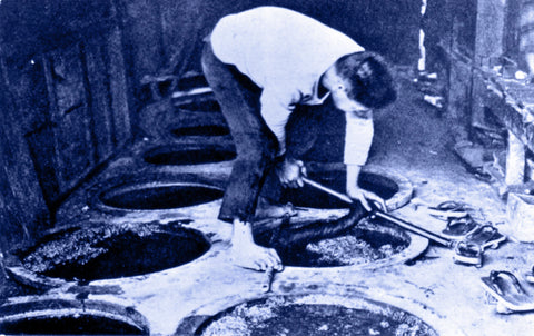 indigo hued black and white image of a man dyeing fabric in indigo dye pits in Okinawa before 1946