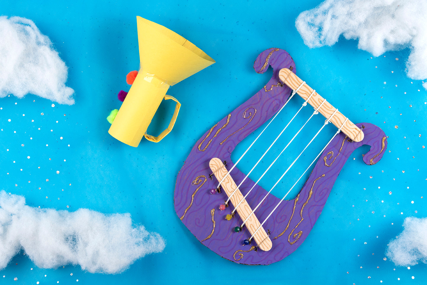 Kid's Bible craft praise instruments against a blue sky background with clouds and glitter rain