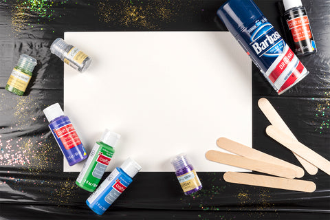 Overhead shot of materials needed for a shaving cream painting on a black trash bag background