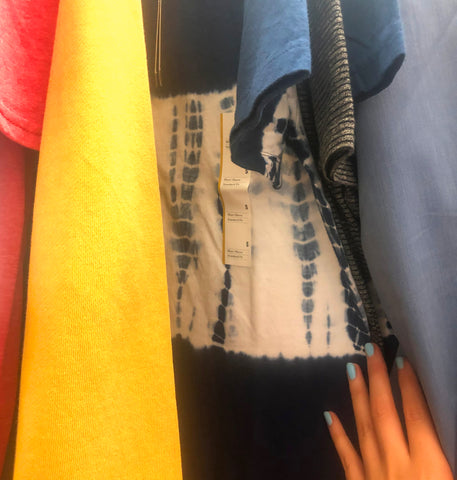 Closeup of Shibori tie dye style top on a garment rack between red, yellow, and grey shirts at Target