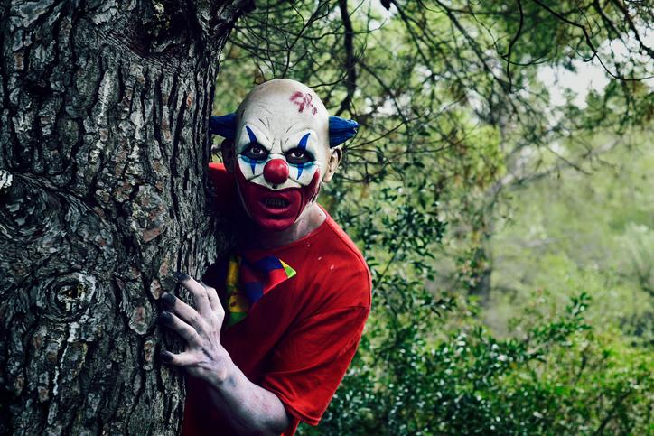 Scary Horror Clown Behind Tree