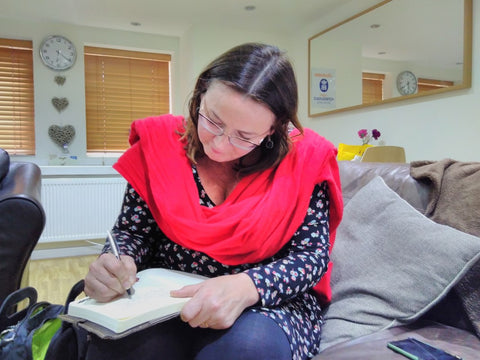 Dr Sara Parker writing in The Little Fair Trade Shop guest book April 2017 - Manchester UK