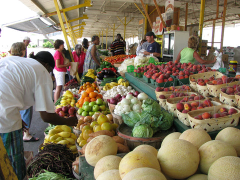 People gathered at a fresh produce stand at a Farmer's Market.
