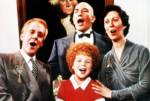Scene from Annie, three adults gathered around a redheaded girl and singing together.