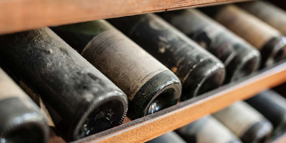 A wine cellar with aging wines gathering dust on a rack.