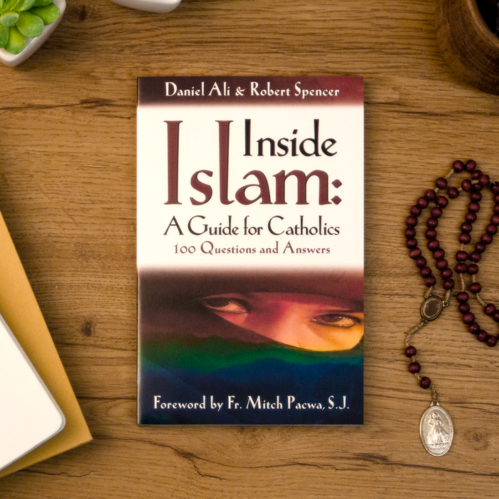 A tabletop lifestyle shot of the catholic book, Inside Islam: A Guide for Catholics by Daniel Ali and Robert Spencer published by Ascension, sitting on a wooden table next to a rosary. The cover features a muslim.