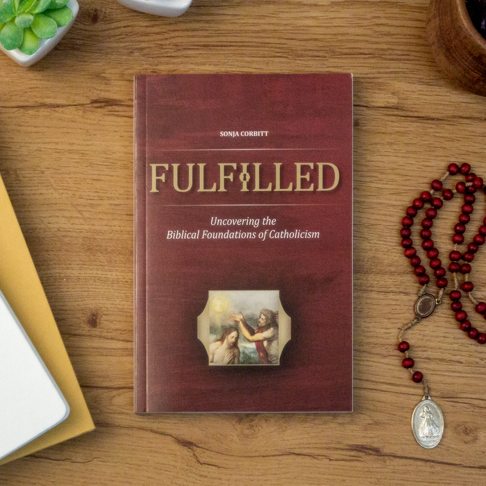 A tabletop lifestyle shot of the Catholic book, Fulfilled: Uncovering the Biblical Foundations of Catholicism by Sonja Corbitt, sitting on wooden table next to a red rosary. The red cover features the Baptism of Jesus at the Jordan.