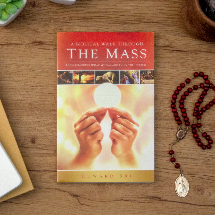 The Catholic book, A Biblical Walk Through the Mass: Understanding What We Say and Do in the Liturgy by best-selling Catholic author Edward Sri and Ascension, sitting on top of a wooden table. The book cover features a priest elevating the Eucharist, an image of the cruxcifixion, and other Catholic scenes.