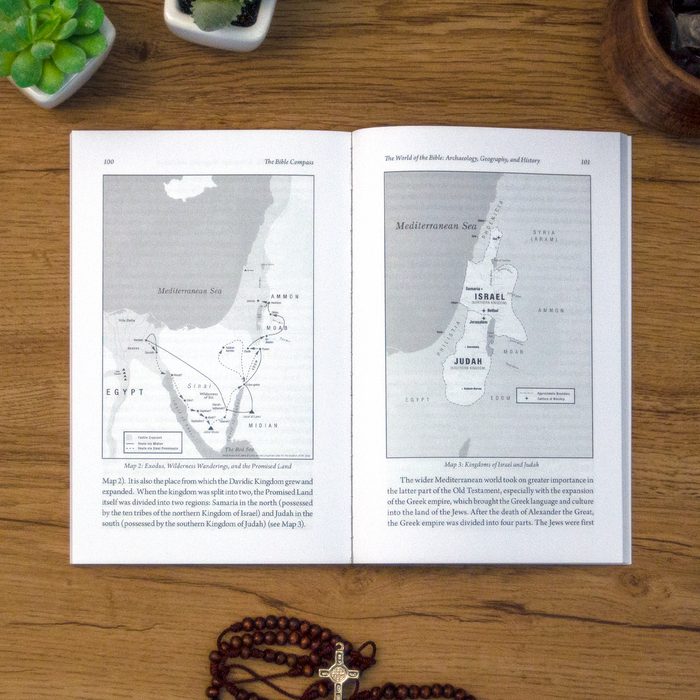 A tabletop lifestyle shot of the catholic book, The Bible Compass: A Catholic's Guide to Navigating the Scriptures by Edward Sri published by Ascension, laying open on a wooden table. The pages feature maps.