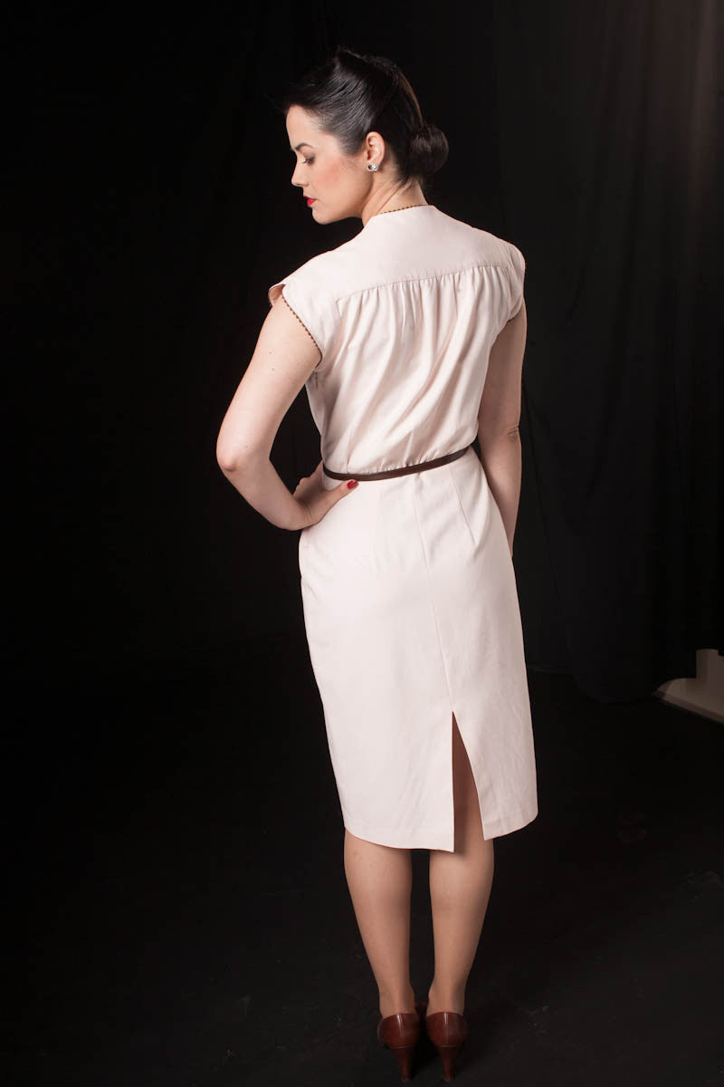 1950's vintage style dress made of slightly stretch light pink fabric, with pencil skirt, and retro detail incorporated on collar and sleeves.