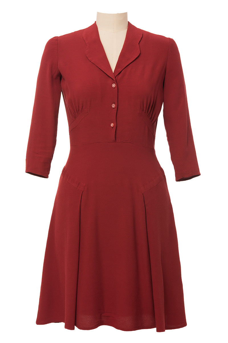 1940s inspired dress made of brick red fabric, 3/4 sleeves. Front view.