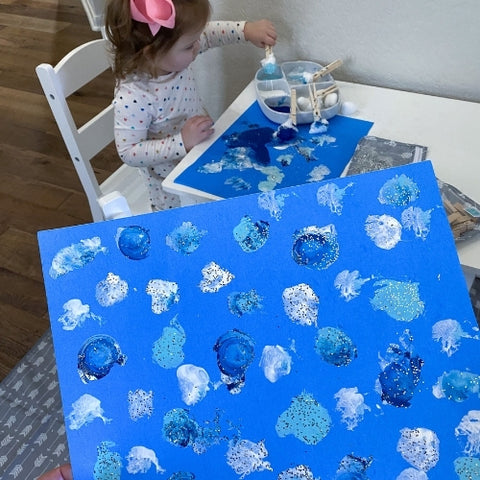 child painting with blue paint and holding a toddler painting