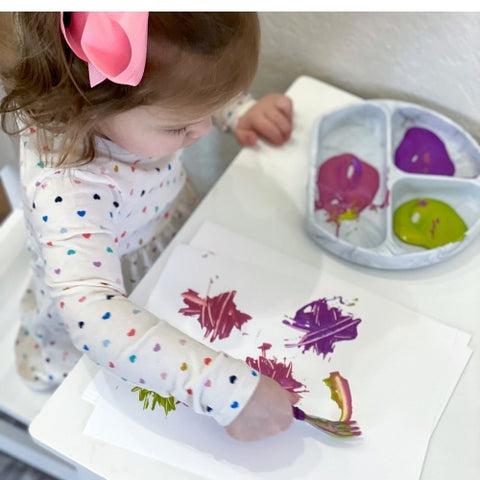 toddler using a fork to paint