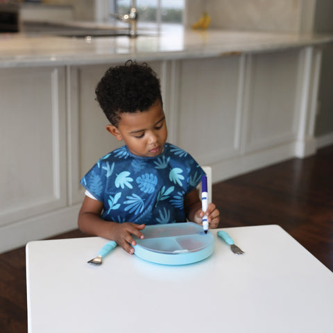 child writing on a divided plate lid