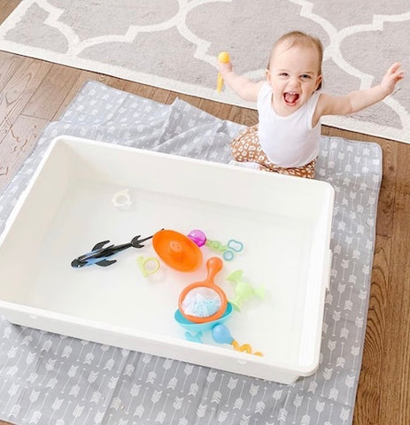 baby playing with toys in water