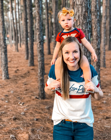 mom with toddler on shoulders in woods