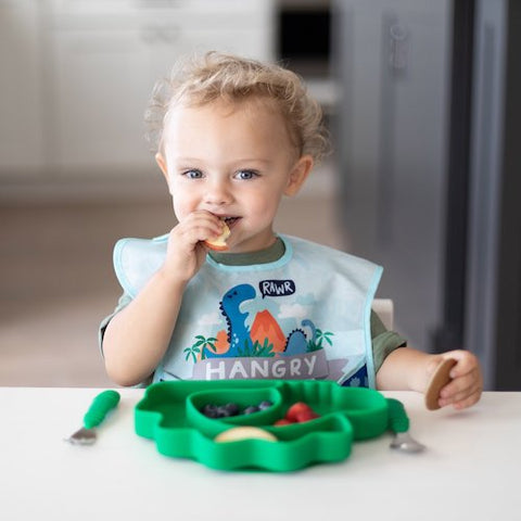 toddler eating out of dinosaur plate in hangry bib