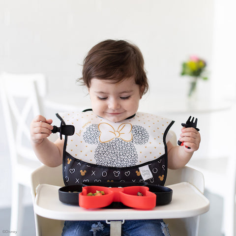 baby in disney black and white bib looking at minnie mouse dish