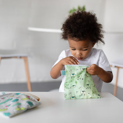 toddler looking in a reusable sandwich bag with llamas on it