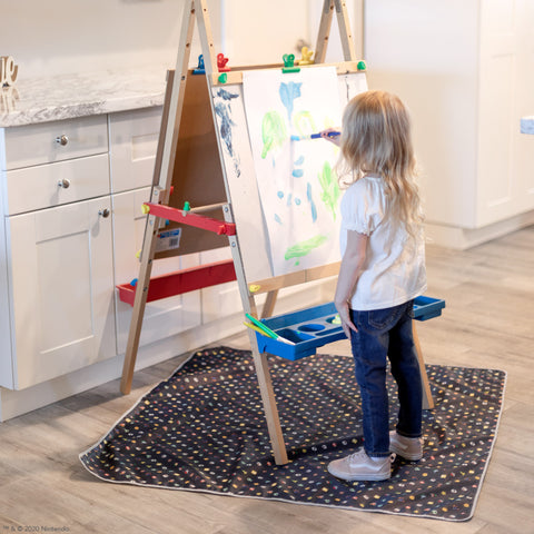 girl painting on top of a super mario splat mat