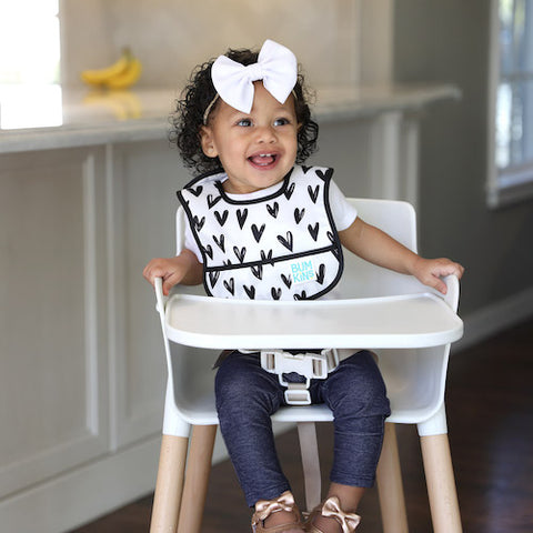 baby wearing a waterproof bib with black and white hearts