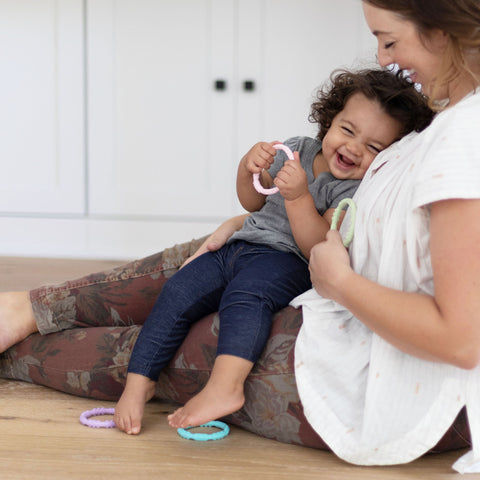 mom holding toddler and laughing