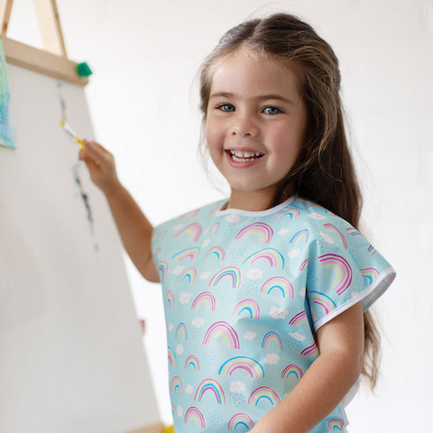 young girl painting in a rainbow art smock