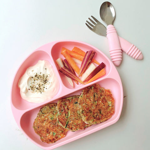 greek zucchini fritters with dip and veggies in toddler plate