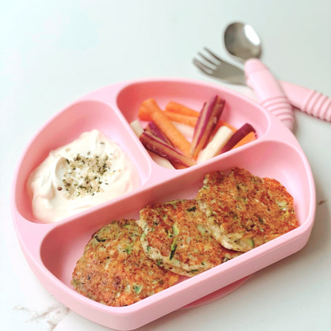 feta zucchini fritters in a toddler plate with veggies and a dip