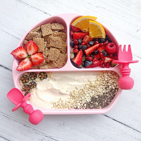 pink toddler silicone plate with yogurt granola cereal and fruit