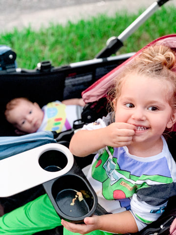 toddler eating snacks while riding in a stroller