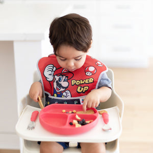 toddler eating wearing a super mario power up bib