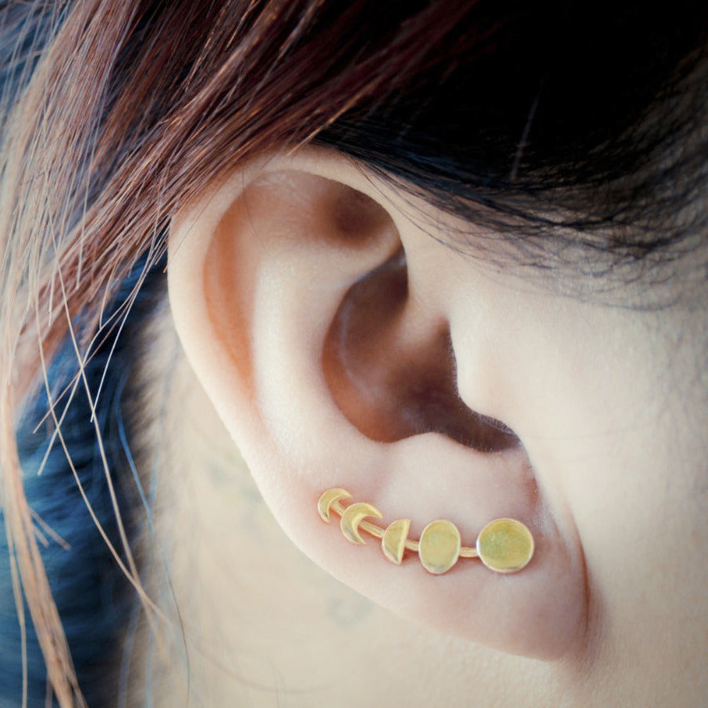 woman wearing gold earring set