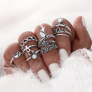 woman's hand with painted white fingernails wearing silver ring set