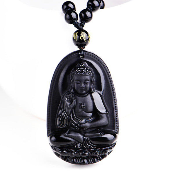black buddha pendant necklace with beads in front of white bowl