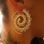 woman with tattoo wearing gold spiral earring