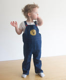 small child wearing overalls