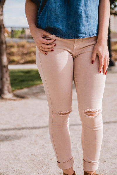 blush pink mid rise skinny jeans with knee slits
